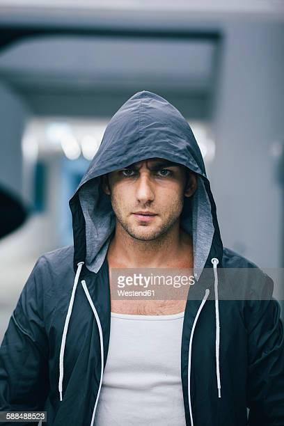 Portrait of angry looking man wearing black hooded jacket