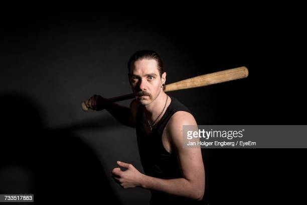portrait of angry man with baseball bat standing against black background - bate de béisbol fotografías e imágenes de stock