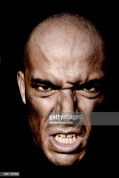 Portrait of Angry Man's Face Against Dark Background