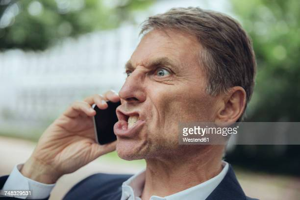 portrait of angry mature businessman outdoors on the phone - shouting stock photos and pictures