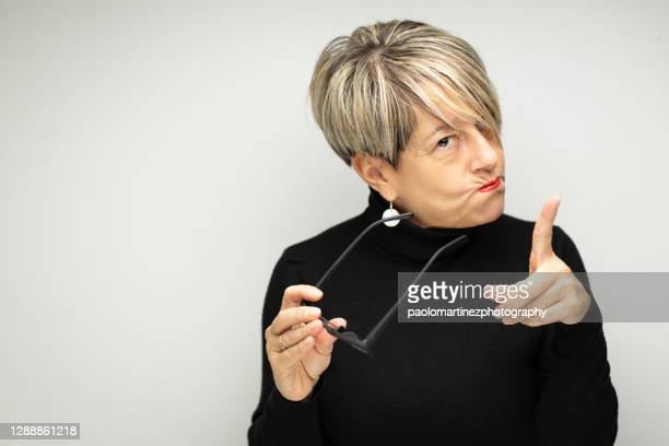 portrait of angry mature woman against white background - sneering stock pictures, royalty-free photos & images