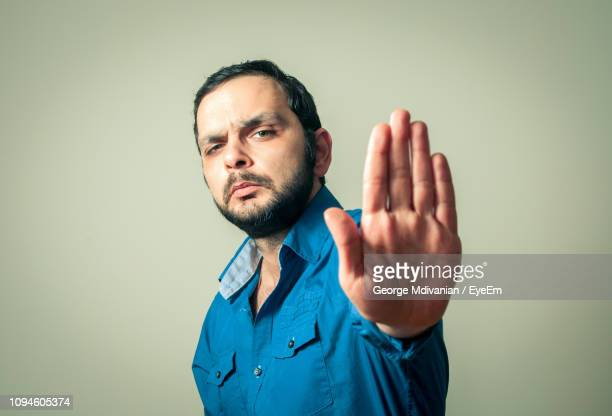 portrait of angry mid adult man showing stop gesture against gray background - weigeren stockfoto's en -beelden