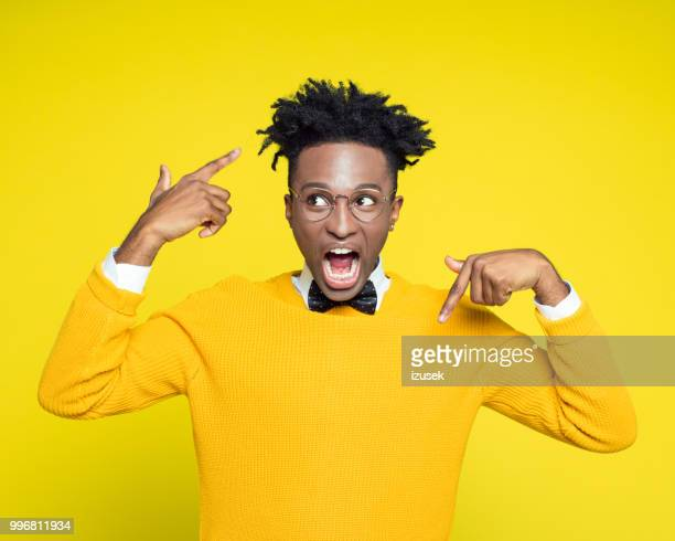 portrait of angry nerdy young man gesturing against yellow background - human finger stock photos and pictures