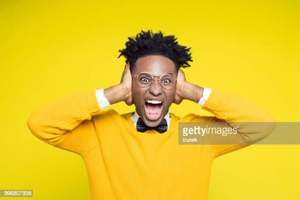 Portrait of angry nerdy young man shouting against yellow background