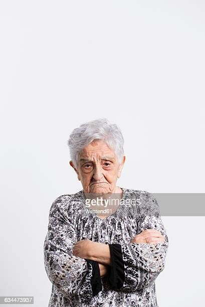 Portrait of angry senior woman in front of white background