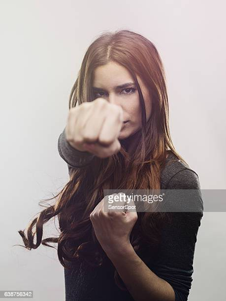 portrait of angry woman punching the air - punching stock pictures, royalty-free photos & images