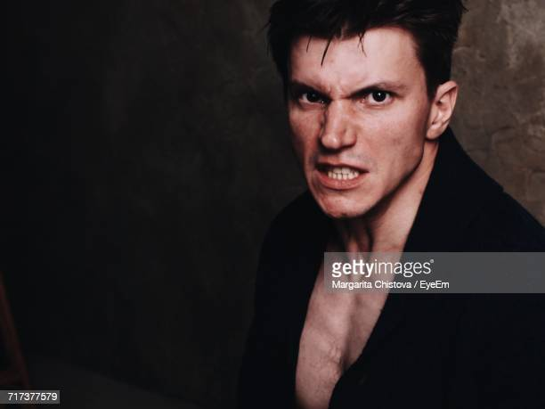 Portrait Of Angry Young Man Against Wall