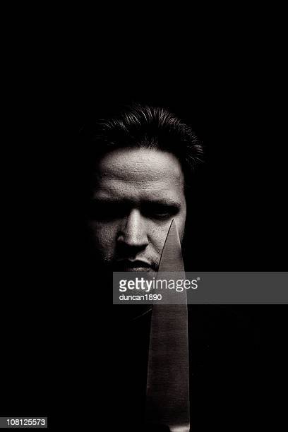 Porträt von Angry Young Man Holding Messer, Low Key