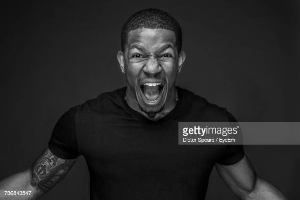 portrait of angry young man shouting against black background - shouting stock photos and pictures