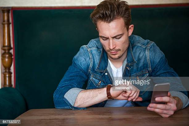 Portrait of angry young man sitting in a coffee shop checking the time