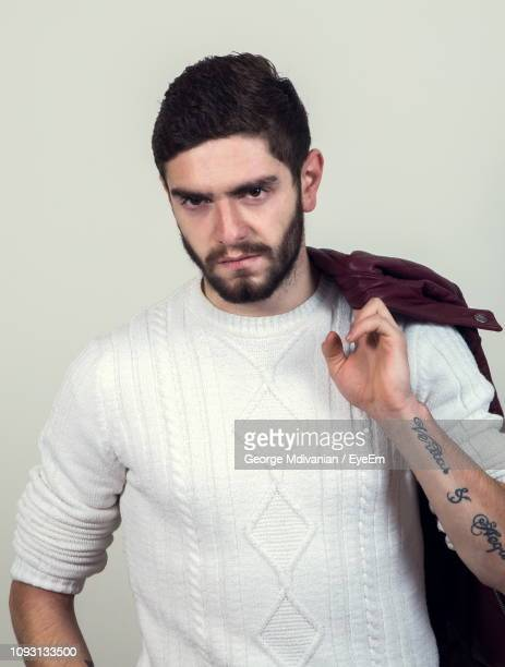 portrait of angry young man standing against gray background - 激怒 ストックフォトと画像
