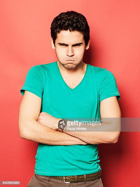 Portrait of angry young man with puffed cheeks standing arms crossed against red background