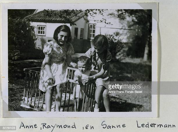 Portrait of Anne Frank and her friend Sanne Ledermann with Sanne's todler brother in a play pen taken from Anne's photo album Beekbergenn Holland