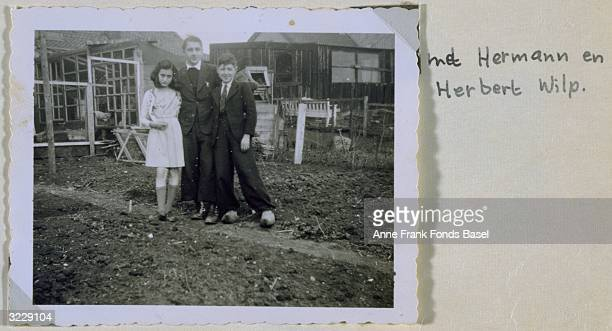 Portrait of Anne Frank flanked by Hermann and Herbert Wilp in a garden with handwritten caption taken from her photo album Amsterdam