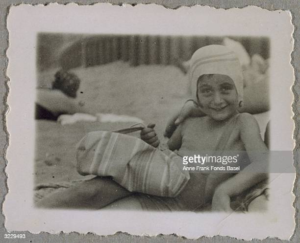 A portrait of Anne Frank lying on a beach in her bathing suit and cap and holding a bag possibly in Zandvoort the Netherlands From Anne Frank's photo...
