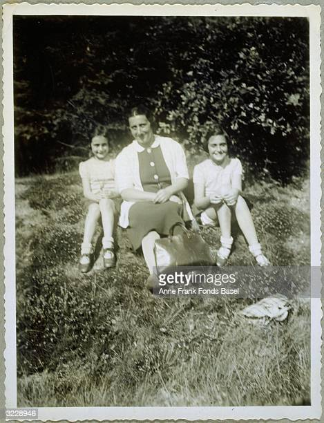 A portrait of Anne Frank sitting with her mother Edith and her sister Margot in the grass near Villa Laret SilsMaria Switzerland From Anne Frank's...