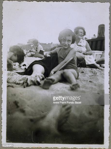A portrait of Anne Frank wearing a bathing suit sitting on a beach amongst other people possibly in Zandvoort the Netherlands From Anne Frank's photo...