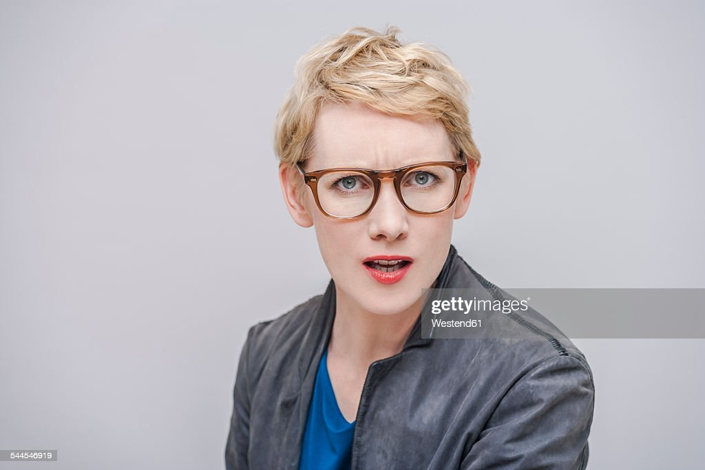 Portrait of annoyed blond woman in front of grey background : Stock Photo