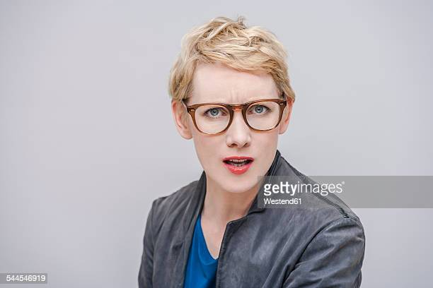 Portrait of annoyed blond woman in front of grey background