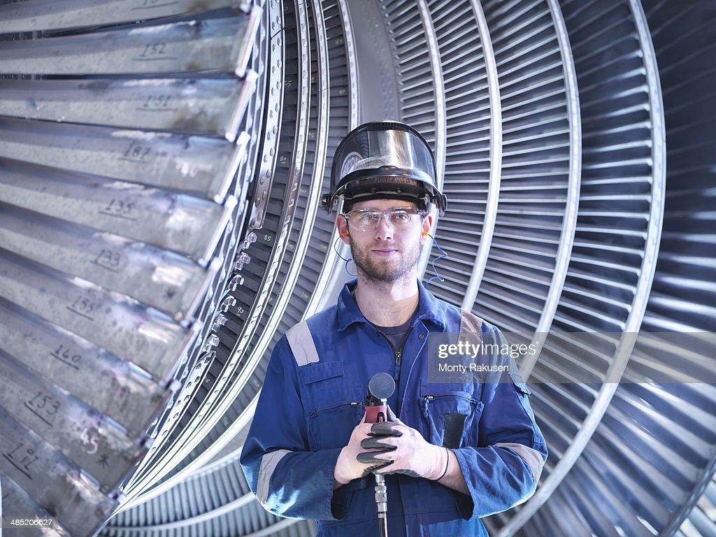 Portrait of apprentice engineer in steam turbine repair workshop : Photo