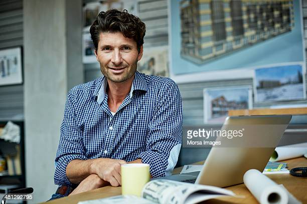 portrait of architect at workstation - architect stockfoto's en -beelden