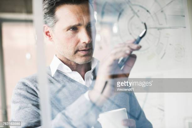 portrait of architect checking construction plan on glass pane in office - business strategy stock pictures, royalty-free photos & images