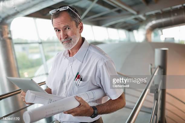 porträt eines architekten mit der pläne liegen vor, und digitale tablet - architekturberuf stock-fotos und bilder