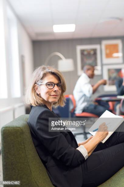 Portrait of architect writing in notebook