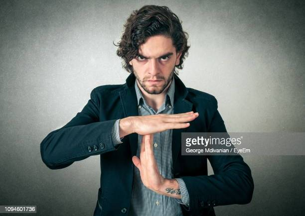 portrait of arrogant young businessman gesturing against gray background - letter t stock pictures, royalty-free photos & images