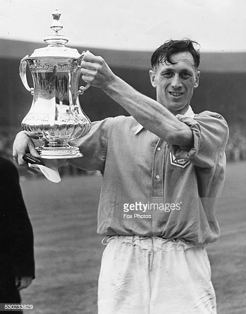 Portrait of Arsenal Football Club captain Joe Mercer smiling as he holds up the FA Cup following the teams win April 29th 1950