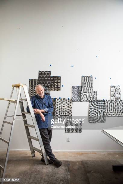 Portrait of artist leaning against ladder and smiling in studio filled with prints