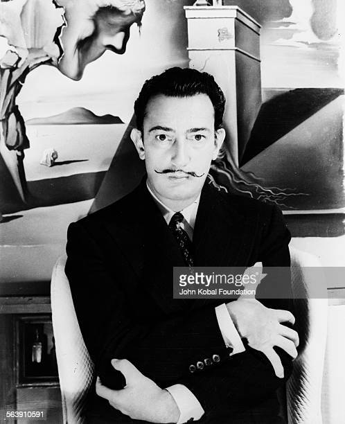 Portrait of artist Salvador Dali standing in front of one of his paintings circa 1950