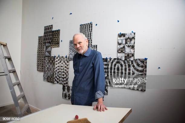 Portrait of artist with hand on work table in studio with artwork on the wall