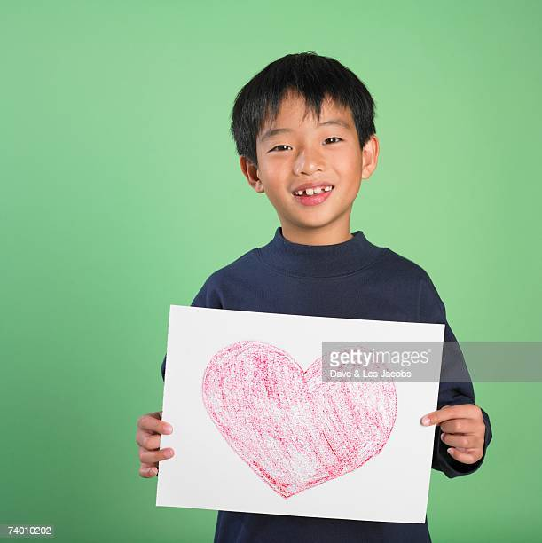 Portrait of Asian boy holding heart drawing