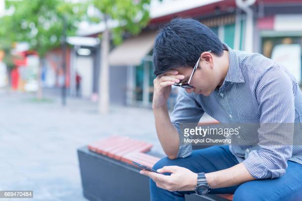 Portrait of asian business man reading message with smart phone in outdoor.
