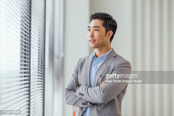 portrait of asian businessman at office - chinese ethnicity stock pictures, royalty-free photos & images