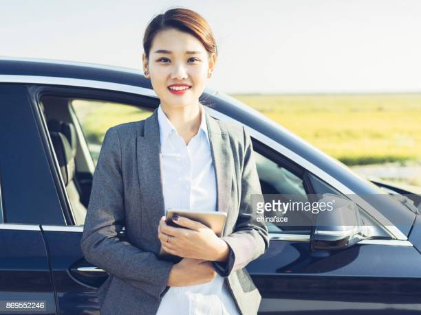 portrait of asian businesswoman holding tablet PC standing by automobile