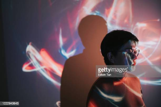 portrait of asian chinese woman with projector reflect image on wall - illuminated stock pictures, royalty-free photos & images
