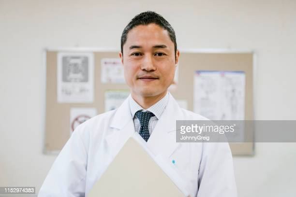 カメラを見てノートを保持しているアジアの医師の肖像 - 白衣 ストックフォトと画像