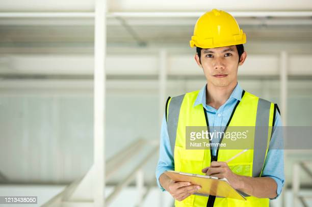 portrait of asian factory engineer in safety uniform while note data on clipboard. cheerful engineer looking at camera working at factory. - タイ人 ストックフォトと画像