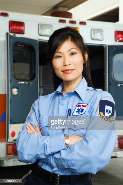 Portrait of Asian female paramedic in front of ambulance