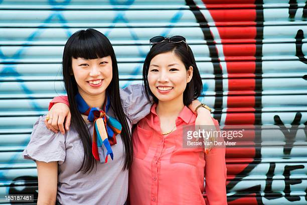 Portrait of asian friends in front of graffiti.l