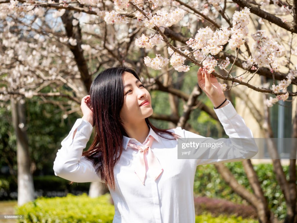 Portrait of asian girl student in school uniform japanese style, smiling among blossom cherry tree brunch in spring garden, beauty, summer, emotion, expression and people concept. : Stock Photo