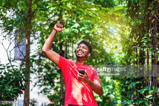 portrait of asian indian man celebrating good success with fist on the air - omar shamsuddin stock pictures, royalty-free photos & images