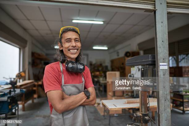 portrait of asian male carpenter at his studio workshop - kuala lumpur stock pictures, royalty-free photos & images