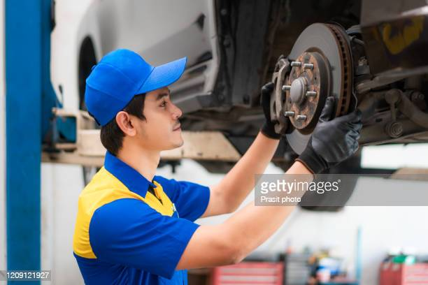 portrait of asian man car mechanic in blue uniform is checking and repairing disc break from vehicle while working in auto service. repair, car service and maintenance concept. - spare part stock pictures, royalty-free photos & images
