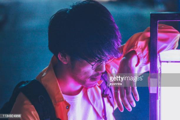 portrait of asian man with neon illuminated - neon stock pictures, royalty-free photos & images