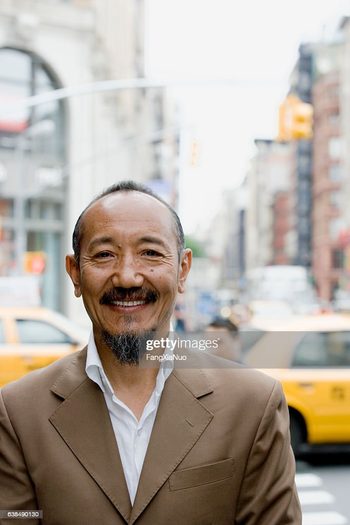 Portrait of asian mature man in downtown city : Stock Photo