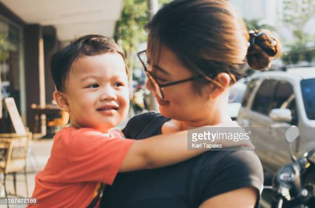 portrait of asian mother and son outdoors - daily life in philippines stock pictures, royalty-free photos & images