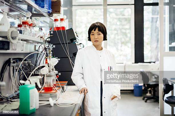 Portrait of Asian scientist standing in laboratory